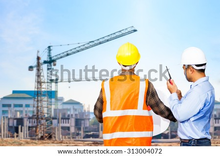 Engineer and foreman looking at blueprints use radio communication for command working against building construction crane