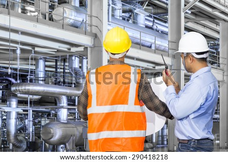 Engineer and foreman working with equipments and machinery in a industrial factory