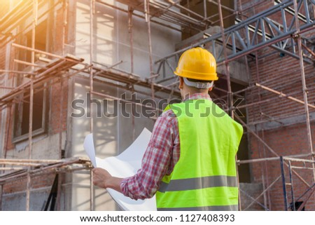 Engineer architect on a building construction site #1127408393