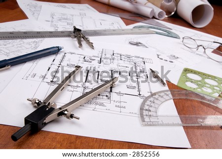engineer, architect or contractor plans and tools laid out on a wooden table - stock photo