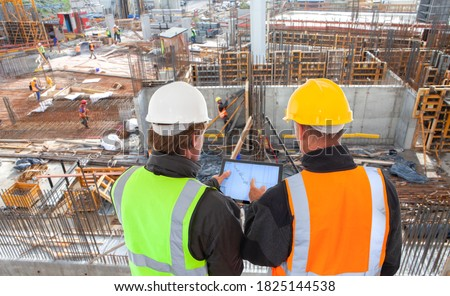 engineer architect with hard hat and safety vest working together in team on major construction site on computer tablet Foto stock ©