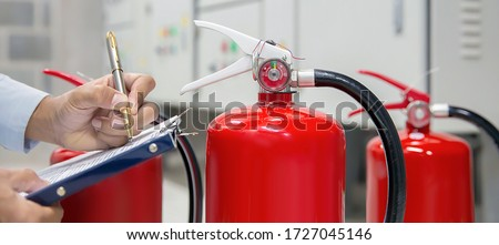 Photo of  Engineer are checking and inspection a fire extinguishers tank in the fire control room for safety training and fire prevention.