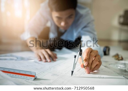 Engineer asia man discussing about building plan for construction at job site, working on desk.Selective focus #712950568