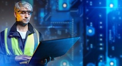Engineer at technological enterprise. Production worker with laptop. Modern production worker concept. Male engineer in yellow vest. Technological Engineer Career. Blurred PCB in background.