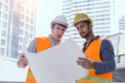 Engineer boss and Engineer worker collaborate, working together at worksite. Employer guy explain project or planning. Blue collar workers working, reading on blueprint. Worker and boss are good team