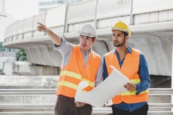 Engineer boss and foreman or worker working together at worksite in city. Employer guy pointing finger to construction for explaining project or plan. Blue collar worker hold blueprint, safety hats