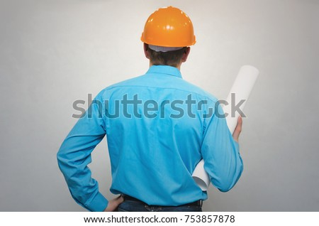 Engineer builder with project drawnings looking forward back view isolated. Construction people. #753857878