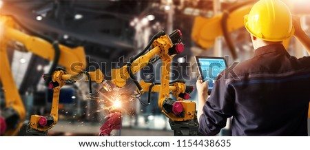 Engineer check and control welding robotics automatic arms machine in intelligent factory automotive industrial with monitoring system software. Digital manufacturing operation. Industry 4.0 Stockfoto ©