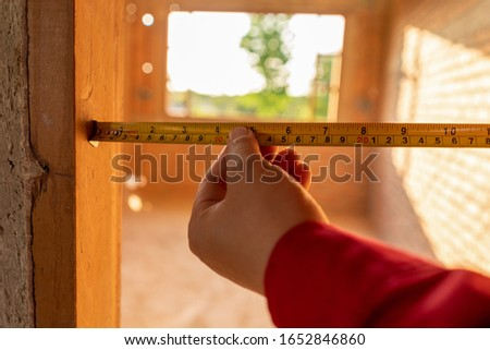 Engineer check length of wood window frame by Tape measure in construction site, Operator working at construction site.