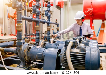 Engineer checking Condenser Water pump and pressure gauge , chiller water pump with pressure gauge. System ready.