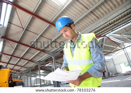Engineer checking plan in building under construction