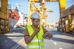 Engineer checking time of Container Cargo freight ship with working crane loading bridge in shipyard