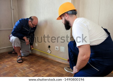 Engineer, contractor and project manager with his colleague, construction worker, handyman and builder is measuring wall room of apartment for renovation using measure tape at construction site.