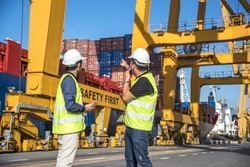 Engineer control Container Cargo freight ship with working crane loading bridge in shipyard