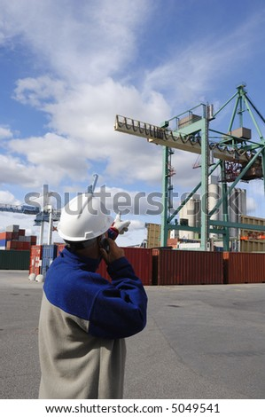 engineer directing large container-crane inside commercial-dock