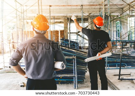 Engineer discussing with foreman about project in building construction site #703730443