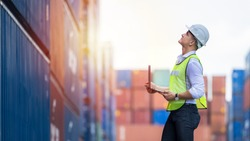 Engineer dock worker wear safety uniform check control loading freight cargo container use computer laptop at commercial dock warehouse, Global business logistic transportation cargo freight shipping.