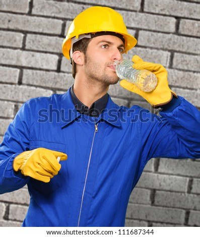 Engineer Drinking Water Near Brick Wall