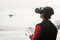 Engineer drone pilot flying with quadcopter outdoor on the beach - Focus on face