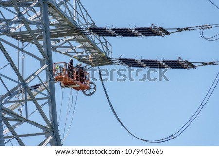Engineer Electrician Workers On Lift Repairing Electricity Pylon Powerline And Wires #1079403665