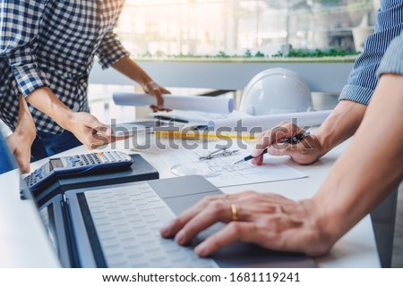 engineer Hand Drawing Plan On Blue Print with architect equipment discussing the floor plans over blueprint architectural plans at table in a modern office stock photo