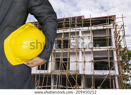 Engineer hand holding yellow helmet for workers security against the background of building under construction  #209450212