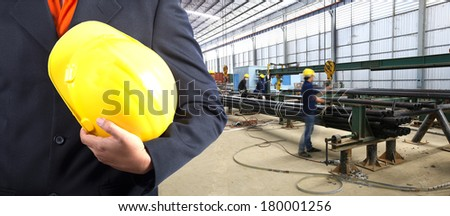 engineer hand holding yellow helmet for workers security against the background of steel pipe packing factory