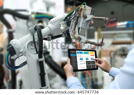 Engineer hand using tablet, heavy automation robot arm machine in smart factory industrial with tablet real time monitoring system application. Industry 4th iot concept.