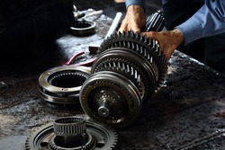 Engineer hands fixing engine power transmission gears box