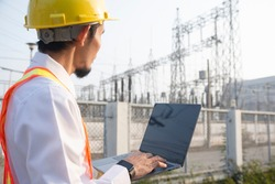 Engineer hold laptop computer inspection on site power plant high volte system