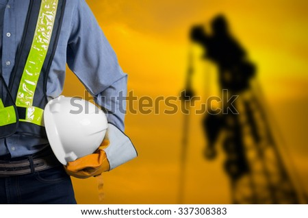 Engineer holding a white helmet for the safety of construction workers on a background crane Silhouette sunset.