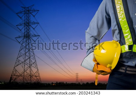 Engineer holding a yellow helmet for the safety of workers on the background Silhouette transmission towers on the background of the evening sun