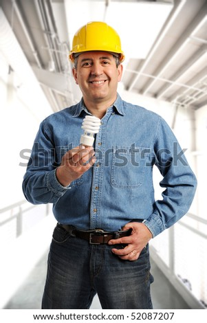 Engineer holding an electrical bulb and wearing a hard hat inside a building
