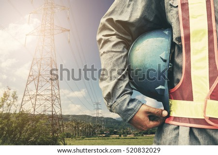 engineer holding blue helmet standing on silhouette high voltage post.High-voltage tower sky background.