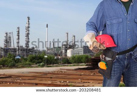 engineer holding red helmet standing in front of site working area