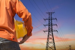 engineer holding yellow helmet standing on silhouette high voltage post.High-voltage tower sky background.