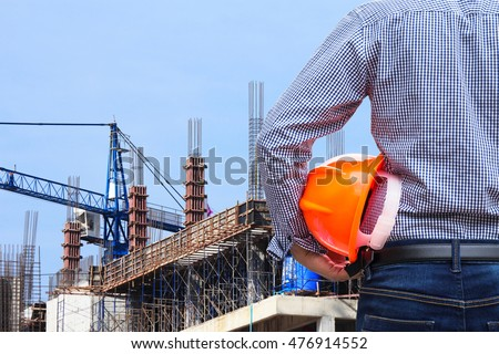 engineer holding yellow safety helmet in building construction site #476914552
