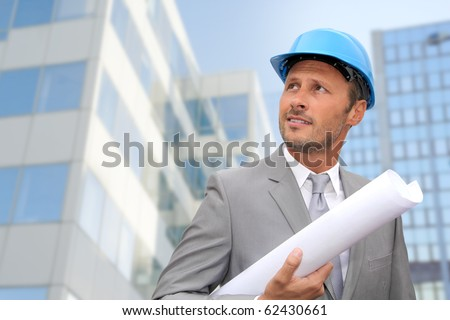 Engineer in front of modern building with plan - stock photo