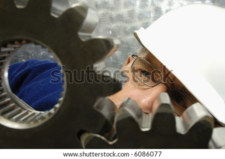 engineer in hard-hat closely examining large industrial gears