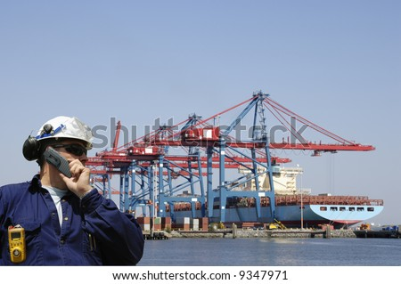 engineer in hard-hat overlooking large commercial container port and ship