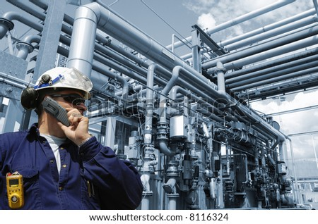 engineer in hard-hat talking in mobile-phone, pipelines in background