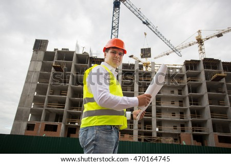 Engineer in hardhat standing on construction site and checking blueprints