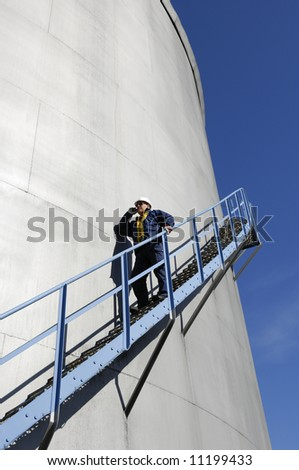 engineer in hardhat, walking along fuel-storage tank
