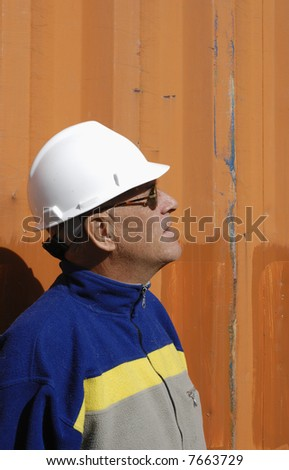 engineer in profile, wearing hard-hat, standing against colored  metal background