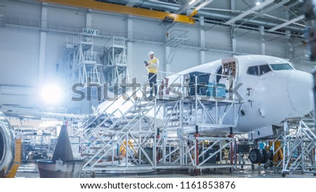 Engineer in Safety Vest Standing next to Airplane in Hangar