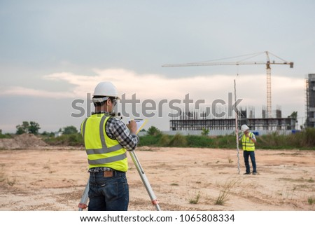 Engineer in the construction measurements using surveying equipment,Land surveyors on the construction,Surveyor equipment #1065808334