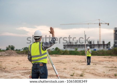 Engineer in the construction measurements using surveying equipment,Land surveyors on the construction,Surveyor equipment #1065808349