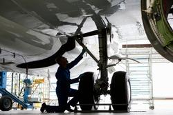 Engineer in uniform inspecting the landing gear of a passenger jet at a hangar.