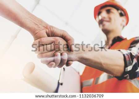 Engineer in Yellow Helmet and Vest Greeted Man with Warm Handshake. Modern Construction and Engineering Concepts. Safety of Work in Production and Construction. Hard Work on Project. #1132036709