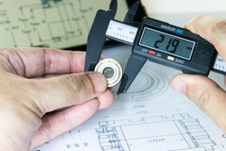 Engineer is measuring dimensions of small bearing with digital vernier caliper equipment and design drawing